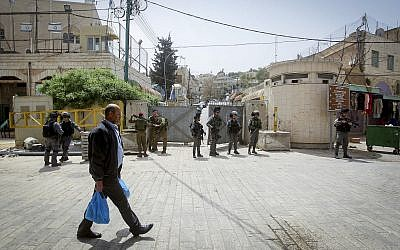 A Palestinian man walks by Israeli troops standing guard in the West Bank city of Hebron. (Photo by Wisam Hashlamoun/Flash90)
