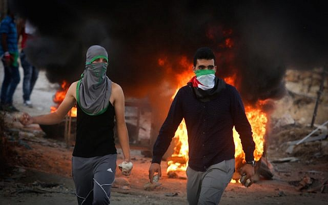 Palestinian protesters throwing stones and burning tires during clashes with Israeli security forces over the Al-Aqsa mosque compound, close to the Israeli manned checkpoint of Hezma in the West Bank, September 30, 2015. (Photo from Flash90)