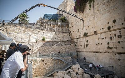 A crane removes a chunk of stone dislodged from the Western Wall in Jerusalem at the mixed-gender prayer section in July. (Photo by Hadas Parush/Flash90)