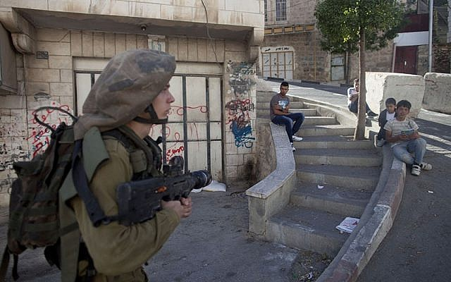 Palestinians watching an Israeli soldier on patrol in a street on September 23, 2013 in Hebron, West Bank. (Photo by Lior Mizrahi/Getty Images)
