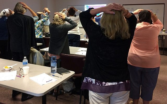A group of tutors in the Pittsburgh OASIS Intergenerational Tutor Program join in a game of Simon Says as part of their training. (Photo by Toby Tabachnick)