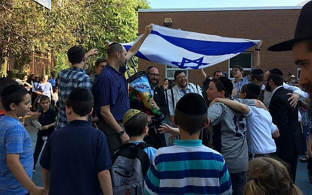 Hillel Academy boys welcome a Torah scroll to the new building. (Photo by Toby Tabachnick)