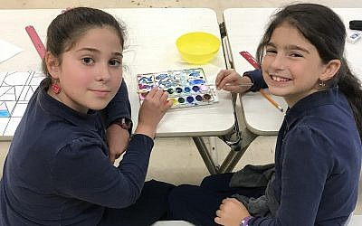 Fifth-graders Chana Katz and Perri Berelowitz bond over a mutual love of art and a shared watercolor palette. 	(Photo by Micki Myers)