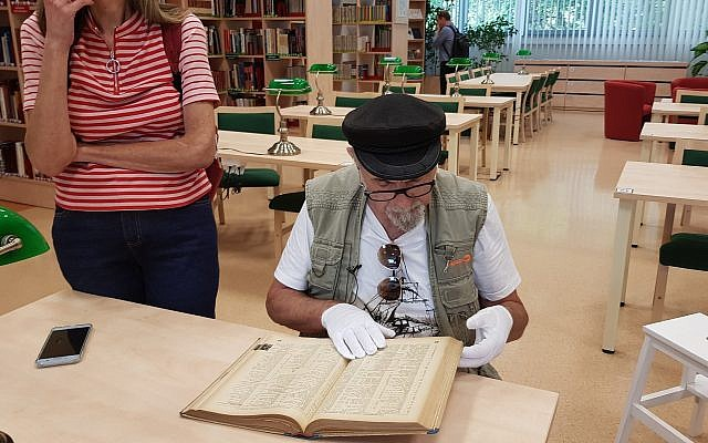 Yoram Sztykgold examines the unpublished registry from 1939 that helped him locate his family's assets at a military library in Warsaw, Sept. 4, 2018. (Photo by Cnaan Liphshiz)