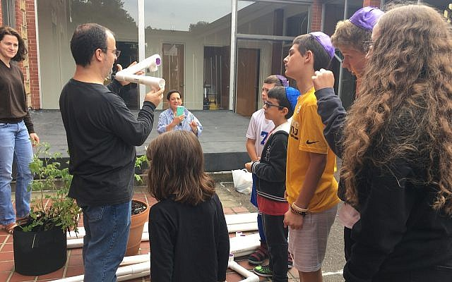 Parent Ben Binus illustrates how the PVC pipes will fit together in the new sukkah he designed. (Photo courtesy of Congregation B'nai Abraham)