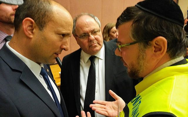 Israeli Minister Naftali Bennett, left, and Consul General of Israel in New York Dani Dayan hear from Rabbi Elisar Admon about local efforts to respectfully clean the site of Saturday's attack.  (Photo by Adam Reinherz)
