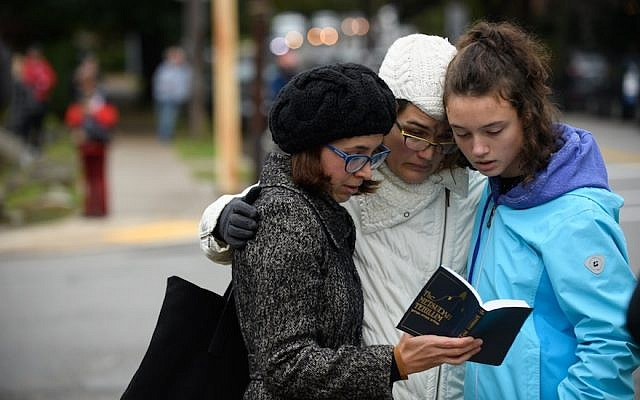 From left: Tammy Hepps, Kate Rothstein and her daughter, Simone Rothstein, 16, pray a block away from the site of a mass shooting at the Tree of Life Congregation in the Squirrel Hill neighborhood of Pittsburgh, Oct. 27, 2018. (Photo by Jeff Swensen/Getty Images)