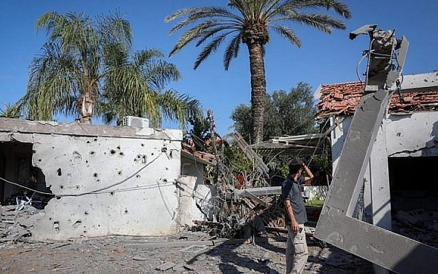 A man stands outside a house that was hit by a rocket fired from the Gaza Strip in the southern Israeli city of Ashkelon. (Photo by Nati Shohat/Flash90)