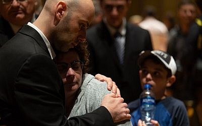 People comfort one another during a vigil for the Tree of Life victims at the Soldiers & Sailors Memorial Hall on Sunday, Oct. 28, 2018. (Photo by Joshua Franzos)
