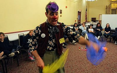Nimi, a medical clown, tosses kerchiefs as Hillel Academy of Pittsburgh students laugh. (Photo by Adam Reinherz)