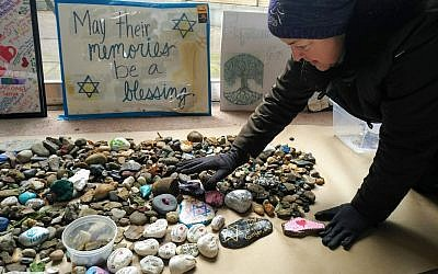 Suzanne Schreiber, a past president of Tree of Life, smooths stones inside the synagogue's space. Items were transported indoors and placed on butcher block paper in order to dry. Photo by Adam Reinherz