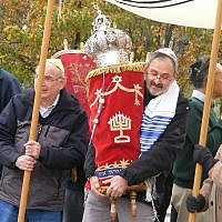 Dr. Richard Gottfried carries the Torah during a procession from New Light Congregation's old building toward their new space.  (Photo by Barry Werber)