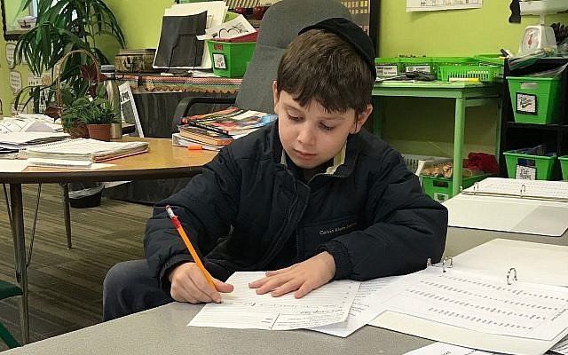 Second-grader Yehuda Yolkut works diligently to create clear, well-written sentences.(Photo by Micki Myers)