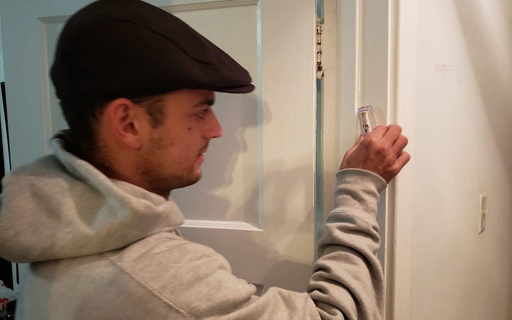 Carnegie Mellon University student Sam Adidas hangs a mezuzah, delivered by Chabad at CMU, onto his doorpost.(Photo provided by Rabbi Yisroel Altein)