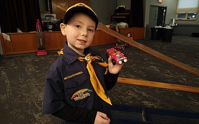 Jacob Greathouse holds a car he and his mother created for Cub Scout Pack 1818's Pinewood Derby. Photo by Adam Reinherz