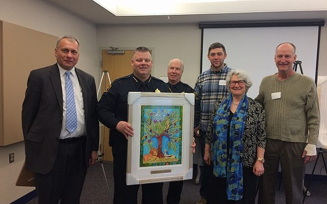 "Rabbi Me'irah Iliinsky presents a framed print of ""The Tree of Life is Weeping"" to the Pittsburgh Police.  (Photo by Toby Tabachnick)"