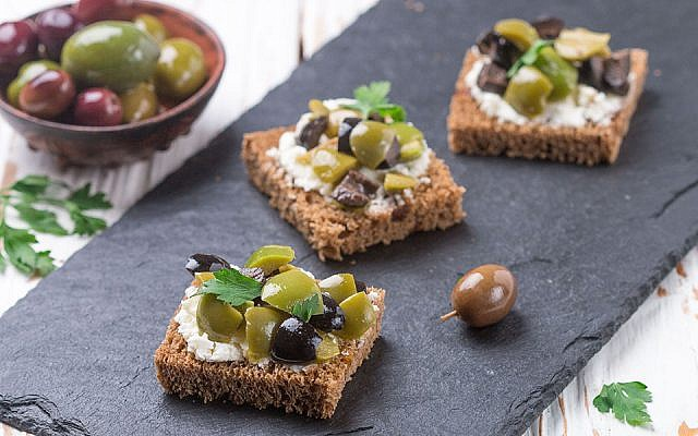 Rye bread toast (canape) with black and green olives, feta cheese and parsley. Tasty snack for gourmets on a slate plate. Selective focus