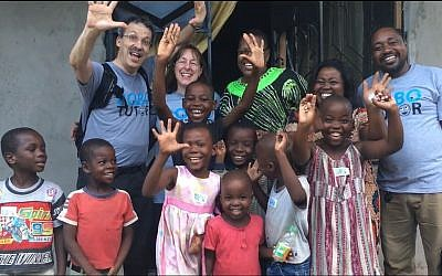 Jack Mostow, his wife, Janet, and Leonora Kivuva in Kidongochekundu, a village near Bagamoyo. Also pictured is a local teacher and some of the children who used RoboTutor. (Photo provided by Jack Mostow)