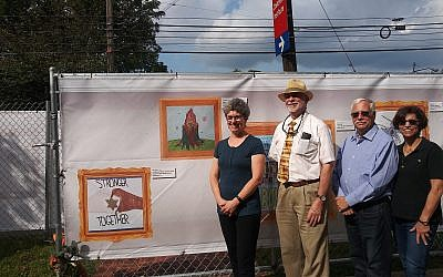 Laurie Zittrain Eisenberg, Rabbi Jeffrey Myers, Stephen Cohen, Ellen Surloff stand next to windscreens with printed art.  Photo by David Rullo