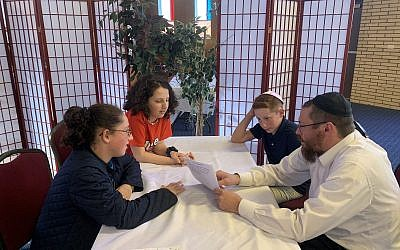 Rabbi Yisroel Altein tutoring Hallie, Samantha and Jack Cohen. Photo courtesy of Jed Cohen
