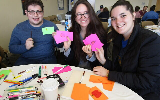 Jonah Lerman, left, Cayla Rubin and Barrie Weiner decorate cards during Hillel Makes a Difference Day.   Photo courtesy of Hillel JUC.