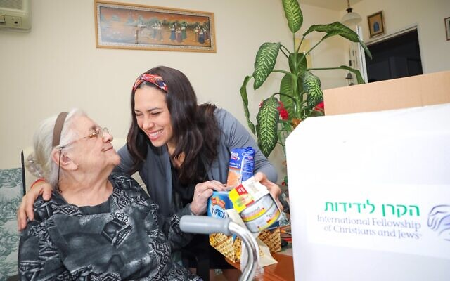 Yael opening food box with elderly woman, Nelli Barotko, glasses, white hair, headband, cane. Holding hands.