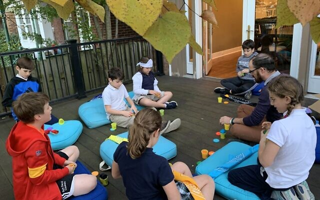 Teacher Chaim Steinberg leads Kesher Kids in a Judaics project.