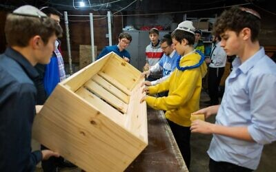 Hillel Academy students help build a casket on Mitzvah Day.   Photo by Joshua Franzos
