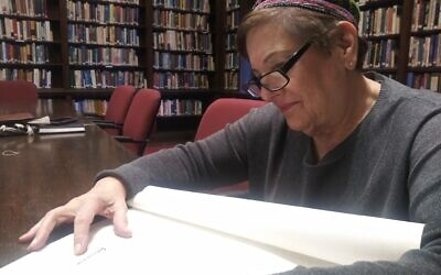 Soferet Linda Coppleson examines the Torah scroll recently started at Temple Sinai. Photo by David Rullo