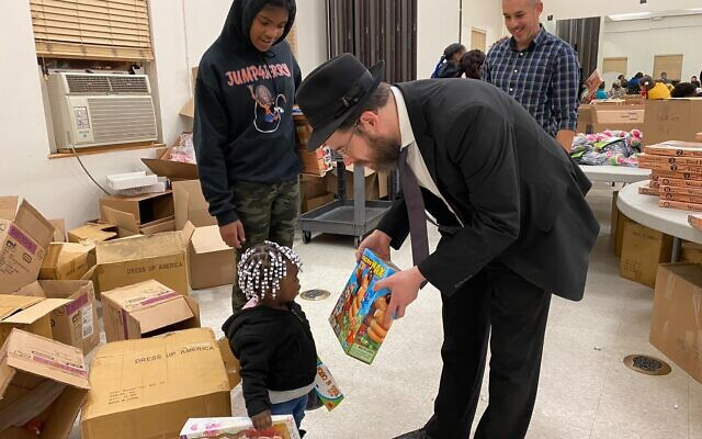 Rabbi Moshe Schapiro shows a toy to a child during the charity drive in Jersey City, New Jersey.  Photo courtesy of Benny Polatseck via JTA.org