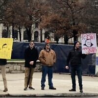 White supremacists stand near Saturday's rally holding anti-Semitic signs. Photo by Mike Elk/Payday Report