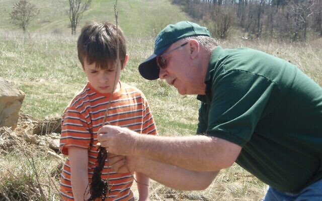 Columbiana County Parks commissioner Mike West demonstrates how to plant a tree to a young volunteer.  Photo by Lisa Butch, Watershed director for the Little Beaver Creek Land Foundation