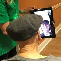 A resident of Charles Morris Nursing and Rehabilitation Center FaceTimes with a relative with the help of a staff member. (Photo provided by the Jewish Association on Aging.)