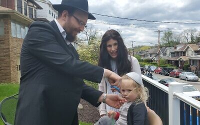 Mannis Frankel cuts the hair of his son Tzvi as his wife Dina looks on. Photo by David Rullo
