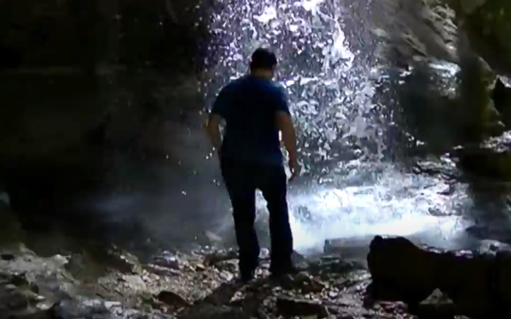 Robert Davis inspects the base of Spouting Rock. Screen grab via YouTube