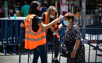 An Israeli woman has her temperature taken before entering the Mahane Yehuda market in Israel, part of a national effort to halt the spread of the coronavirus, June 16, 2020. (Olivier Fitoussi/Flash90)
