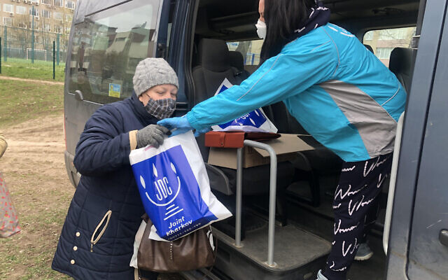 A JDC employee, right, delivers an aid package to a Jewish woman in Kharkiv, Ukraine, March 2020.Photos courtesy of the JDC via JTA.org