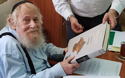 Rabbi Adin Even-Israel Steinsaltz inspects at his Jerusalem home an English-language translation of the Talmud based on his annotations on June 4, 2018. (Wikimedia Commons/SoInkleined)
