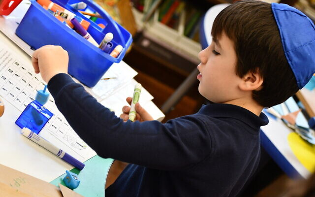 Judah Goldston uses school supplies. Photo courtesy of Community Day School