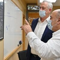 Defense Minister Benny Gantz, with jacket, is briefed on the progress of the development of a vaccine against coronavirus at the Israel Institute for Biological Research by its director general, Shmuel Shapira. (Ariel Hermoni/Defense Ministry)