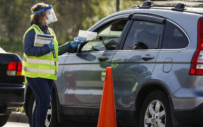 A healthcare worker hands out testing information to people waiting at a drive-through COVID-19 testing site in Chicago, May 6, 2020. (Joel Lerner/Xinhua via Getty via JTA)