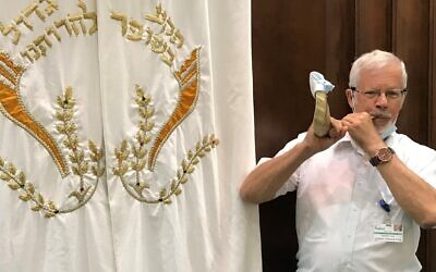 Rabbi Eli Seidman blows a shofar outfitted with a surgical mask. Photo provided by JAA.