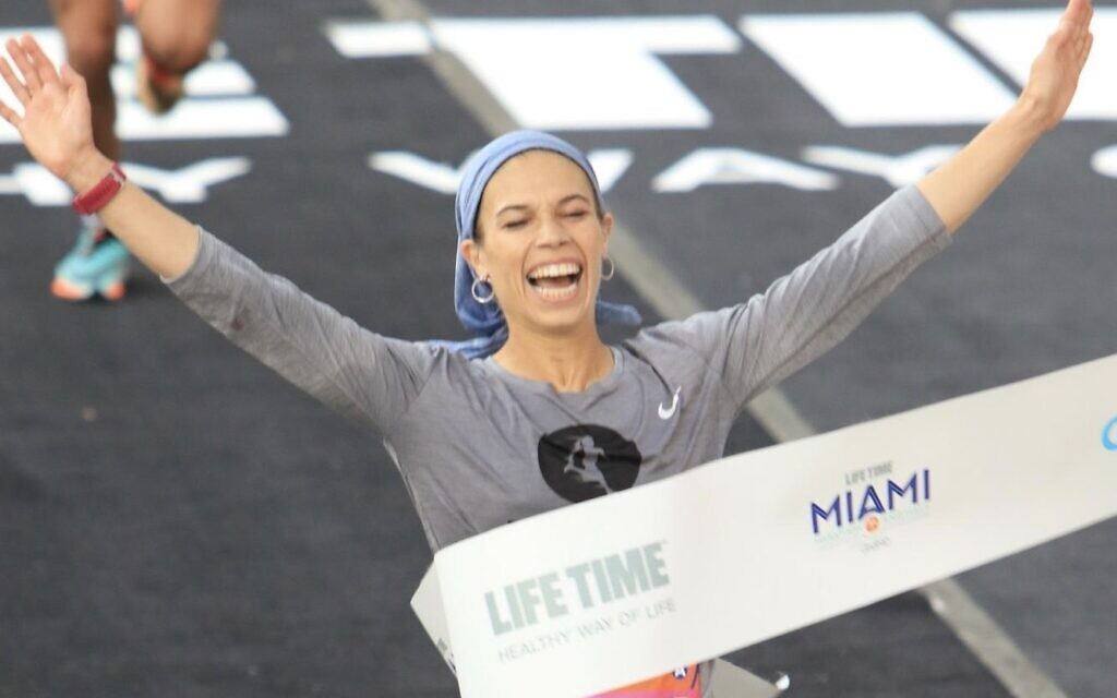Beatie Deutsch crossing the finish line to win the women's category of the 2020 Miami half-marathon race. Photo by Marathon-Photos.