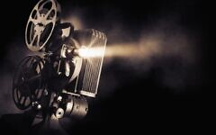 Movie projector on dark background stock photo. Photo by fergregory/iStockphoto.com