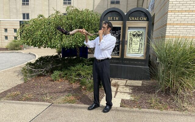 Congregation Beth Shalom's Rabbi Seth Adelson sounds a sock-covered shofar, while standing on Beacon Street in Squirrel Hill. Photo by Jim Busis
