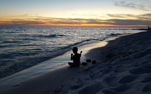 Malori Asman's grandson Riley Herman, now 8, throws rocks into the Gulf of Mexico at sunset for tashlich in Rosemary Beach, Florida in 2016. Photo by Erin Herman.
