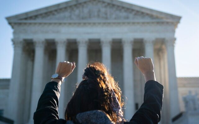 A woman with the pro-life organization Bound4Life raises her hands in prayer outside of the U.S. Supreme Court building, Oct. 5, 2020. (Drew Angerer/Getty Images via JTA)