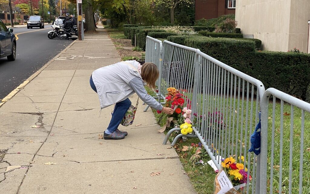Person pauses to read a handwritten note left by the fence barricade outside the Tree of Life building. (Photo by Jim Busis)