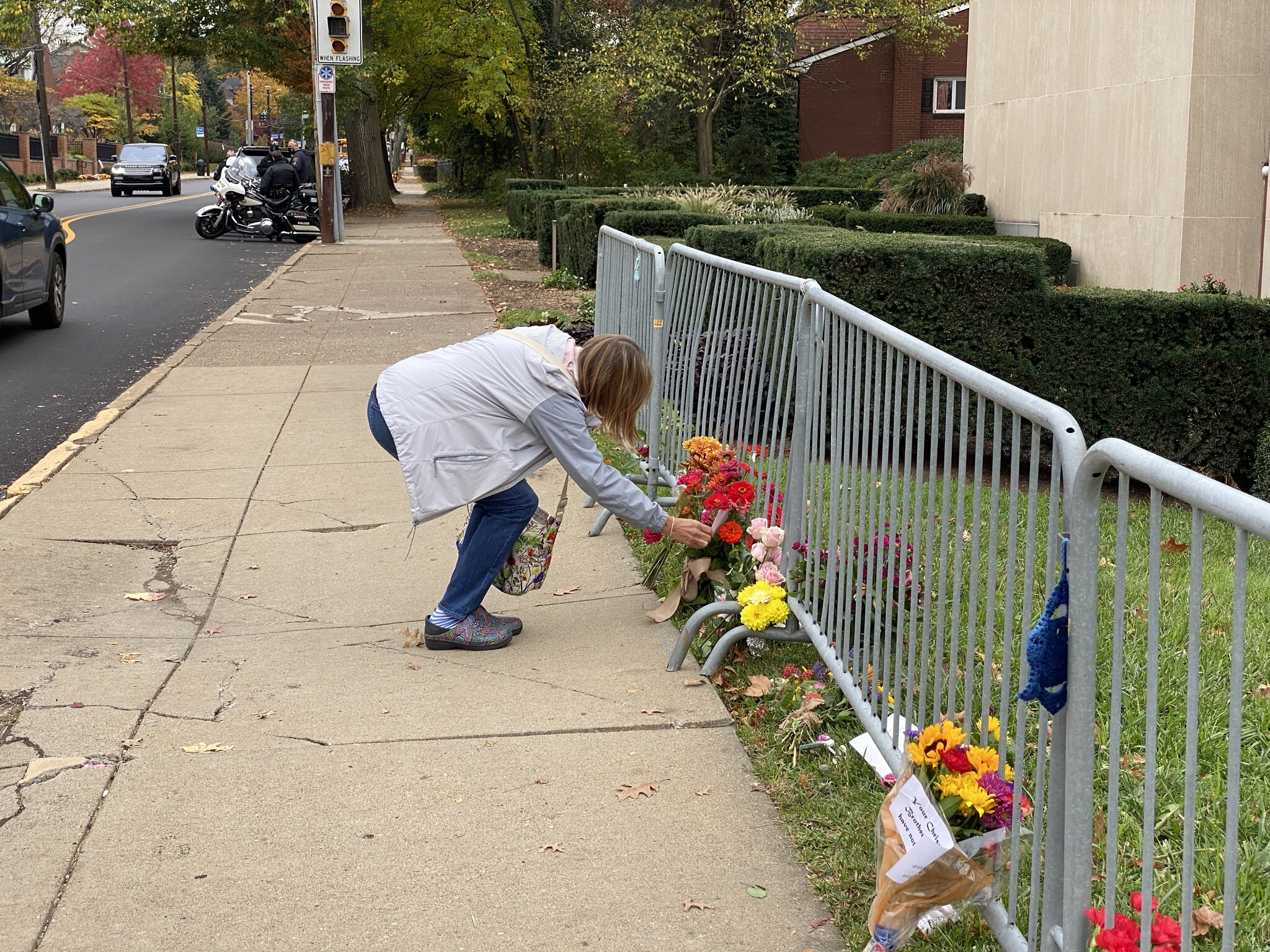 Person pauses to read a handwritten note left by the fence barricade outside the Tree of Life building. Photo by Jim Busis