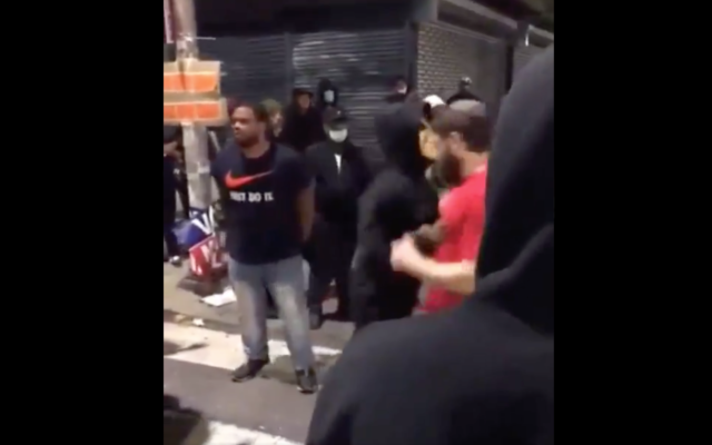 One of the kippah-clad men was pushed (Screenshot from the video attached to Yaacov Behrman's tweet)